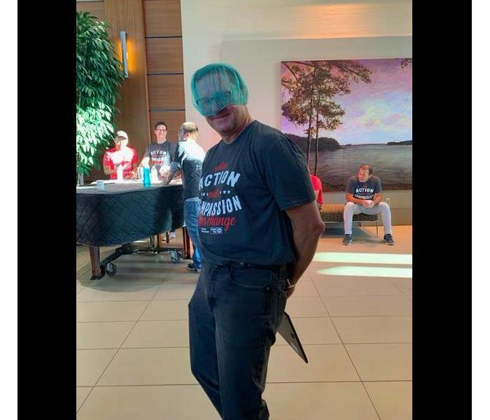 Team member posing with his blue hair net on his head. He is wearing blue jeans and a t-shirt.