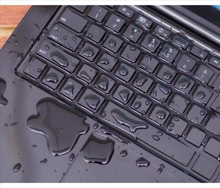 Above view of laptop with water drop damage liquid wet and spill on keyboard,