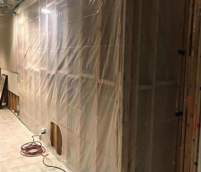 A drywall covered with plastic, this is used as a containment barrier to prevent the spread of contaminants