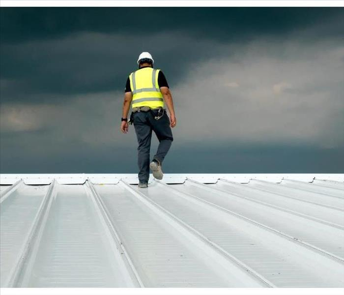 Construction engineer wearing safety uniform inspection metal roofing work for roof industrial